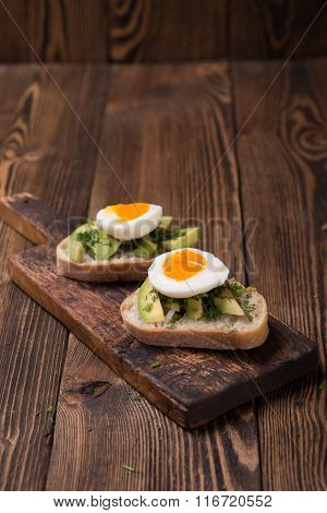 Tasty snack of open sandwich with avocado and soft boiled egg on wooden cutting board