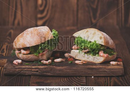 Tasty snack of sandwich with shrimps and soft cheese on wooden cutting board.