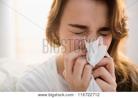 Woman blowing her nose on couch in the living room
