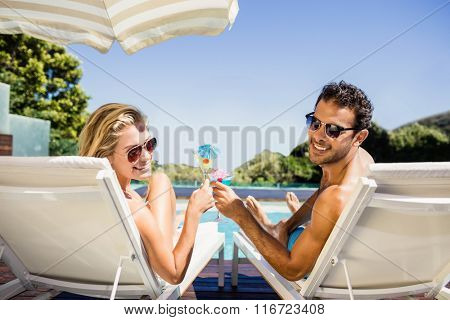 Happy couple on deck chair holding cocktails poolside
