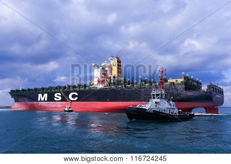 MSC mega container ship pulled by a tugboat into Haifa's commercial port.