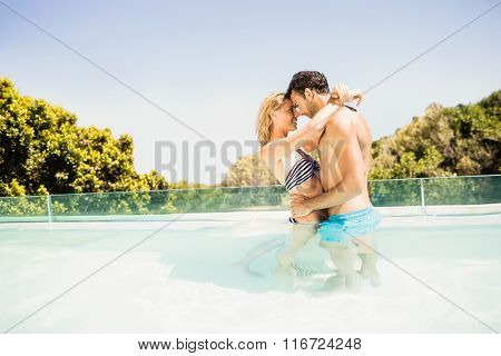 Happy couple embracing in the pool