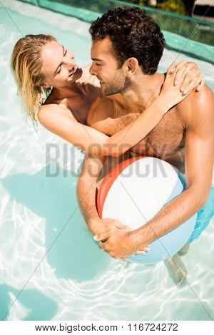 Happy couple with beach ball in the pool