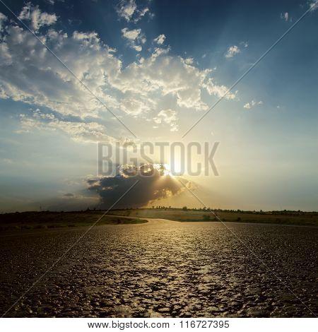 low sun in clouds on sunset over asphalt road. soft focus