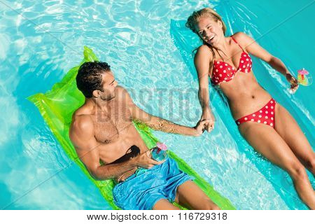 Peaceful couple on lilos holding cocktails in the pool