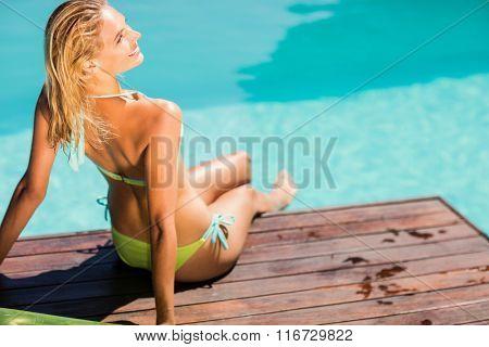 Smiling blonde sitting on pools edge