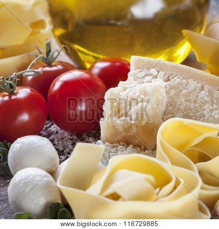 Italian food background.  Parmesan, cherry tomatoes, ribbon pasta, olive oil.