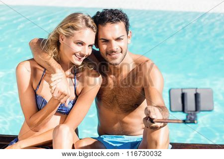 Cute couple taking selfie by the pool
