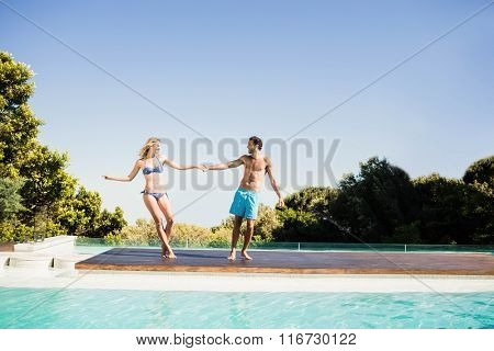 Cute couple holding hands by the pool