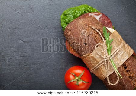 Sandwich with salad, ham, cheese and tomatoes on stone board. Top view with copy space