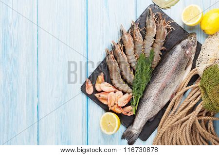 Fresh raw sea food with spices on stone plate over wooden table background. Top view with copy space