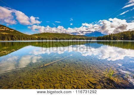 Clear water Pyramid Lake reflects the clouds and pine forests on shore. Frosty morning in the Rocky Mountains, Canada