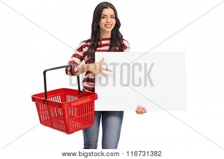 Cheerful young woman holding an empty shopping basket and pointing on a blank banner isolated on white background