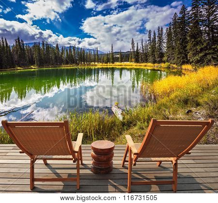 Two wooden deckchairs for tourists on ashore shallow round lake. Autumn day in Jasper  National Park in the Rocky Mountains of Canada