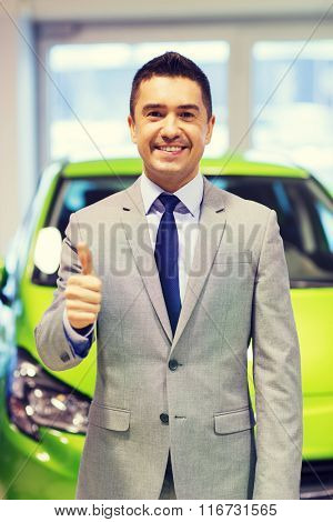 man showing thumbs up at auto show or car salon