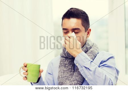 ill man with flu drinking tea and blowing nose