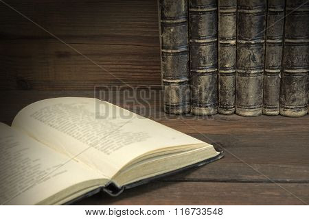 Single Open Book And Old Shabby Books In Row