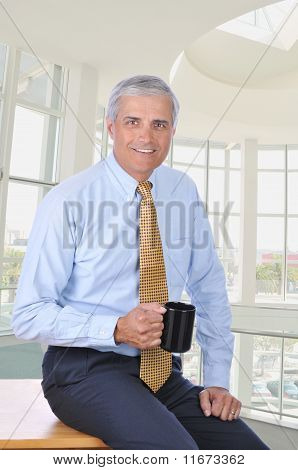 Businessman Sitting On Desk With Coffee