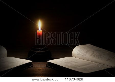 Lighted Candle And Two Open Books On The Wood  Background