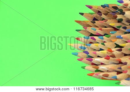 Large Group Of Colored Pencil Isolated On Green Background