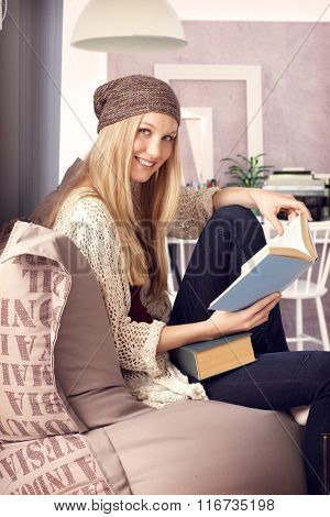 Happy blonde college student learning at home, reading book, looking at camera, smiling.