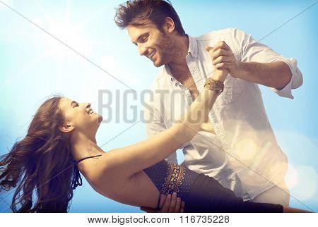 Happy romantic couple dancing open air under blue sky.