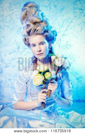 Magnificent young woman in a lush silver and white dress and high elegant hairdo holds a bouquet of white roses and smiling. Beautiful bride portrait, wedding. Ice Queen concept.