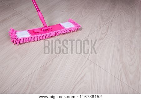 Close Up Of Pink Mop On Wooden Floor