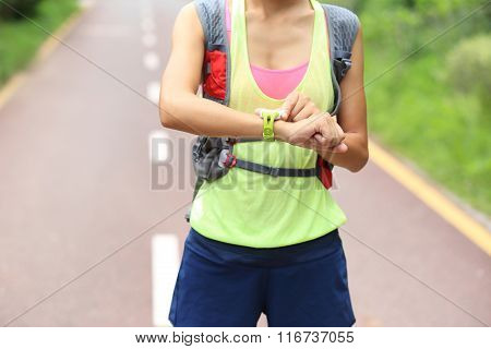 young fitness woman trail runner set her sports watch on trail