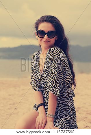 Beautiful Female Model In Fashion Sun Glasses And Dress Sitting On The Sand On Sea Background