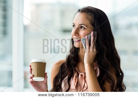 Smiling woman on phone call holding disposable cup against window