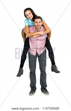 Smiling man giving piggy back to his girlfriend on white screen