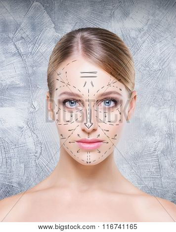 Portrait of attractive, young woman with arrows on face over concrete background. Plastic surgery concept.