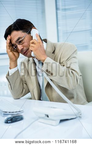 Troubled asian businessman on the phone in his desk