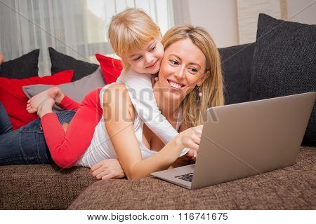 Little girl lying on her moms back while she is using laptop