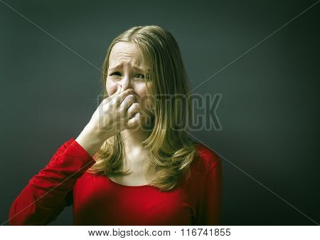 Portrait of a young girl in a red dress on a gray background. Headshot woman pinches nose with fingers hands looks with disgust something stinks bad smell situation.