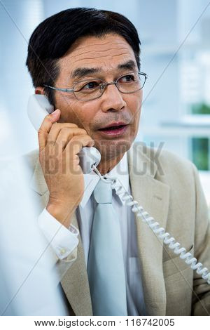 Focused businessman talking on the phone in his desk