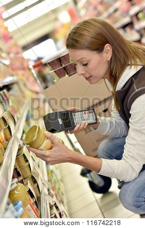 Sales assistant scanning products before putting them on shelves