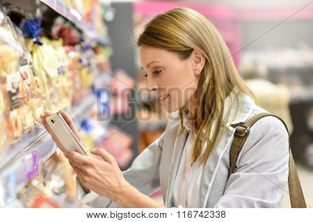 Woman in supermarket checking shopping list on smartphone