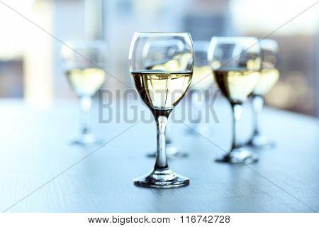 Glasses of wine on light blurred background