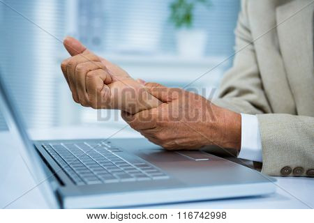 Businessman with wrist pain at his computer