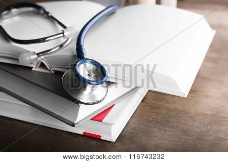 Stethoscope with stack of books on wooden background. Medical literature concept