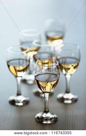Glasses of wine on wooden blurred background