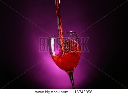 Wine pouring in glass on dark purple background