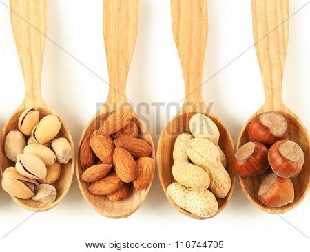 Wooden spoons with hazelnuts, pistachios, almonds and peanuts, isolated on white