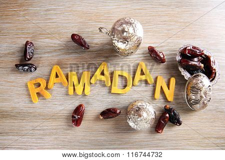 Ramadan word with wooden letters, dishes and dry dates on table