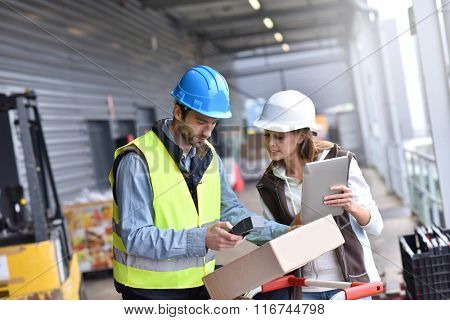 Store manager with warehouseman checking goods reception