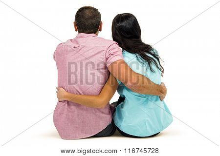 Rear view of couple hugging sitting on white screen