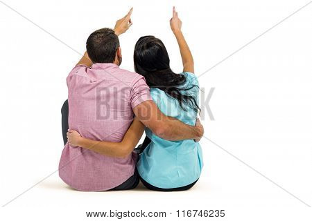 Rear view of couple sitting and pointing somewhere on white screen