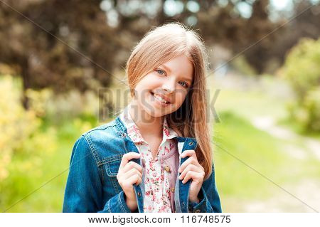 Smiling blonde girl outdoors